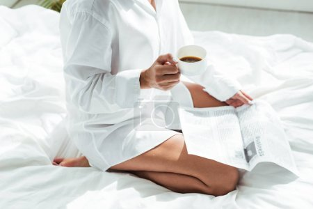 cropped view of woman in white shirt holding cup of coffee and newspaper at morning