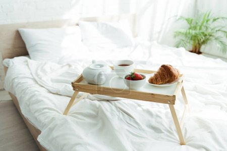 Photo for Wooden tray with teapot, up, croissant and strawberries at morning - Royalty Free Image