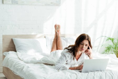 attractive and sad woman in white shirt using laptop at morning