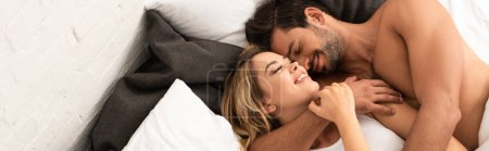Photo pour Happy tendre couple blotti au lit le matin - image libre de droit