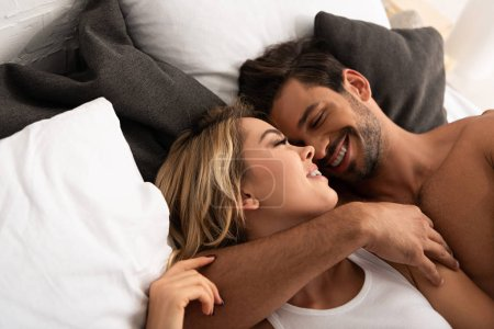 Photo for Smiling tender couple hugging in bed in the morning - Royalty Free Image