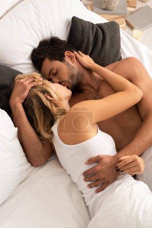 Photo pour Petit couple embrassant et embrassant le lit le matin - image libre de droit