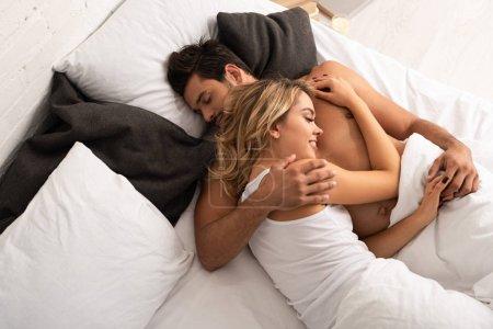 Photo pour Heureux couple souriant blotti au lit le matin - image libre de droit