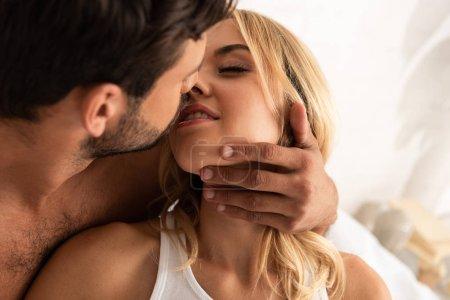 Photo pour Homme embrassant et allant embrasser sensuel femme au lit le matin - image libre de droit