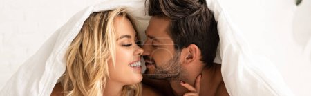 Photo pour Happy tender couple going to kiss under sleeping sheets in the morning - image libre de droit