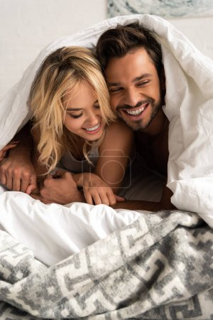Photo for Smiling couple lying under sleeping sheets in the morning - Royalty Free Image