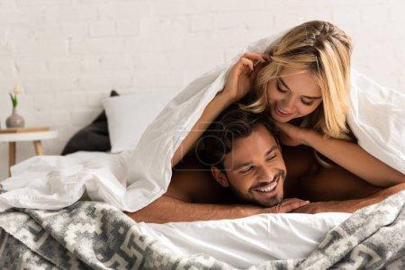 Photo pour Un couple heureux couché sous des draps le matin - image libre de droit