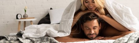 Photo for Beautiful happy couple lying under sleeping sheets in the morning - Royalty Free Image