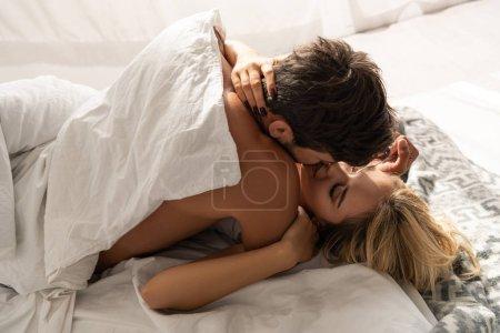 Photo pour Beau couple séduisant embrassant et s'embrassant dans le lit le matin - image libre de droit