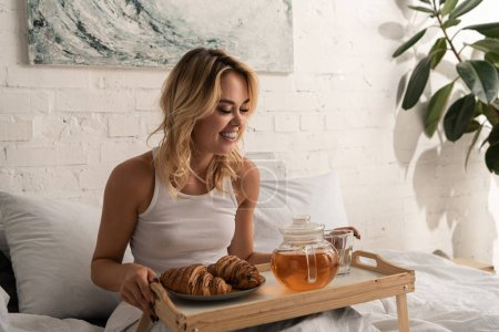 Photo pour Attractive happy girl having croissants and tea for breakfast in bedroom in the morning. - image libre de droit