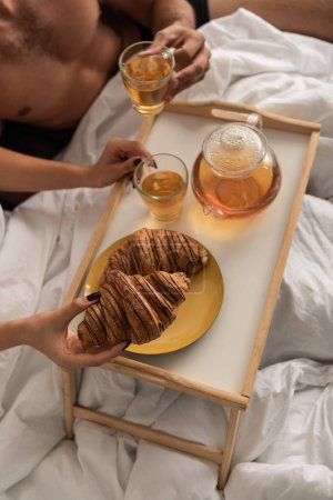 Photo for Cropped view of couple having tea and croissants for breakfast in bed in the morning - Royalty Free Image
