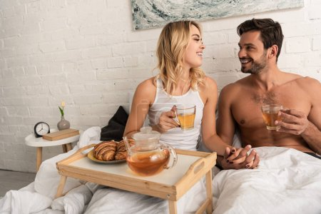 Photo for Happy couple having tea and croissants for breakfast in bed in the morning - Royalty Free Image