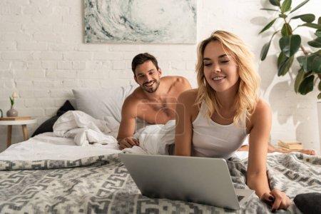 Photo pour Attrayant fille à l'aide d'un ordinateur portable au lit avec petit ami souriant derrière - image libre de droit