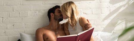 Photo pour Petit couple s'embrassant et tenant un livre au lit le matin - image libre de droit