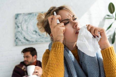 Photo pour Femme malade avec mal de tête tenant pulvérisation nasale et serviettes dans la chambre avec l'homme derrière - image libre de droit