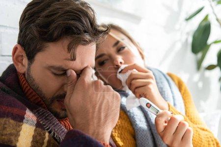 Photo pour Couple malade avec fièvre tenant thermomètre et serviettes au lit - image libre de droit