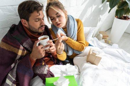 Photo pour Couple malade avec fièvre tenant thermomètre, boisson chaude et serviettes au lit - image libre de droit