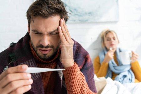Photo pour Homme malade avec maux de tête et fièvre regardant thermomètre dans la chambre à coucher avec femme derrière - image libre de droit