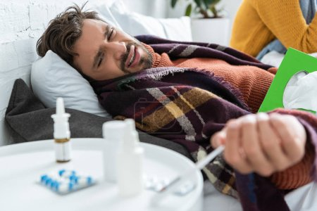 ill man in bed with pills, napkins and nasal spray in bedroom with woman