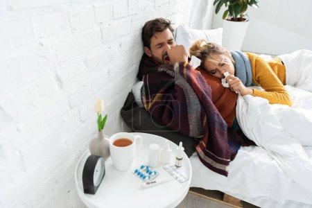 Photo pour Couple malade tenant des serviettes dans la chambre avec thermomètre, pilules, boisson chaude et vaporisateur nasal - image libre de droit