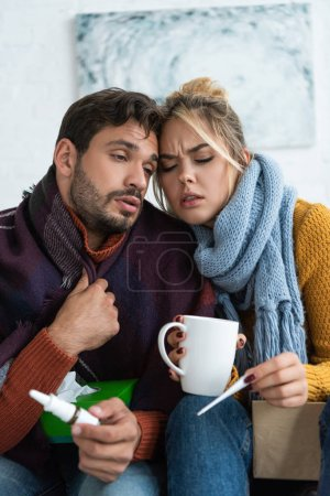 Photo pour Couple malade avec fièvre tenant thermomètre, boisson chaude et pulvérisation nasale - image libre de droit