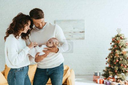 Photo pour Heureux parents se tenant près d'un arbre de Noël décoré et tenant un bébé adorable - image libre de droit