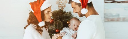 Photo pour Happy woman looking at smiling husband holding little daughter near christmas tree - image libre de droit