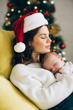 jeune femme en santa chapeau assis avec les yeux fermés et tenant bébé endormi