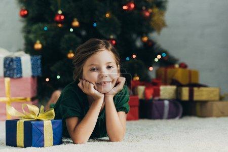 Photo pour Heureux enfant couché au sol près de la boîte à cadeaux et souriant à la caméra - image libre de droit
