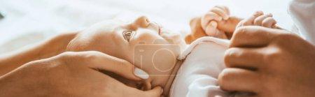 Photo pour Vue recadrée de maman et papa touchant doucement bébé couché sur la literie, plan panoramique - image libre de droit