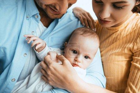Photo pour Vue recadrée du mari heureux et de la femme tenant le petit enfant - image libre de droit