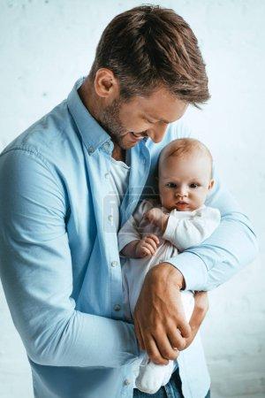 Photo pour Heureux père souriant tout en tenant mignonne petite fille - image libre de droit