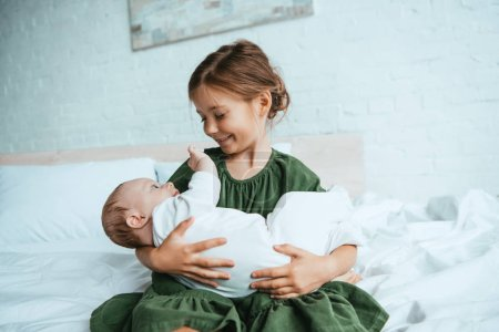 Photo for Happy child holding cute little sister while sitting on white bedding - Royalty Free Image