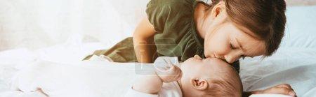 Foto de Foto panorámica de la adorable hermana pequeña besadora que se encuentra en la cama blanca. - Imagen libre de derechos