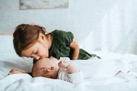 Photo for Adorable child kissing little sister lying on white bedding - Royalty Free Image