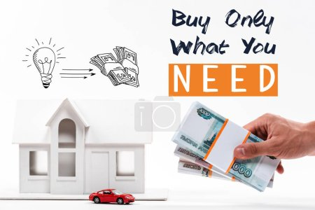 Photo for Cropped view of man holding money near house and car models, buy only what you need lettering isolated on white - Royalty Free Image