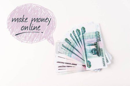 Photo pour Top view of Russian money on white background with make money online lettering in speech bulbble - image libre de droit