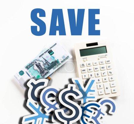 Foto de Vista superior de la calculadora cerca de rublos russianos en fondo blanco con iconos de palabras y divisas salvos. - Imagen libre de derechos