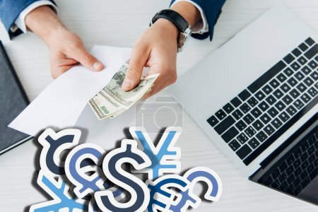Photo pour Top view of business man holding envelope with dollar banknotes near laptop on table with currency signs illustration - image libre de droit
