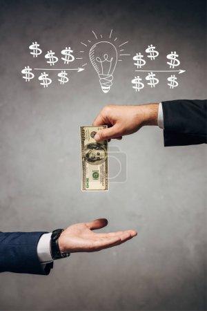 Foto de El hombre de la vista recortada que da dinero a los hombres de negocios en el fondo gris con la bombilla y los signos del dólar ilustran. - Imagen libre de derechos