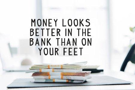 Foto de Los billetes de banco en dólares que están sobre la mesa con dinero se ven mejor en el banco que en la ilustración de sus pies. - Imagen libre de derechos