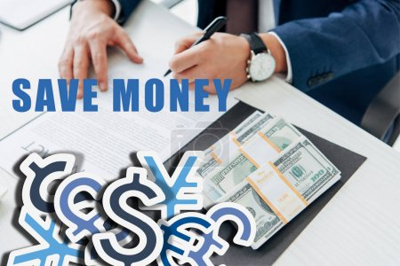 Photo for Cropped view of businessman signing contract near money in office with save money illustration - Royalty Free Image