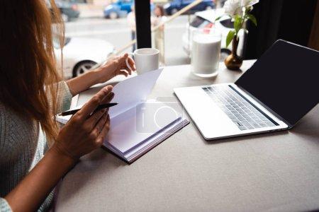 Photo pour Vue recadrée de fille étudiant en ligne avec bloc-notes et ordinateur portable dans le café avec tasse de café - image libre de droit