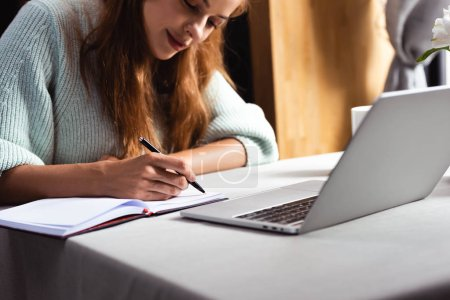 Photo for Redhead woman writing and studying online with laptop in cafe - Royalty Free Image