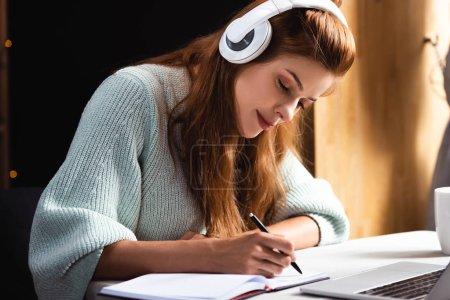 Photo pour Femme dans les écouteurs écriture et étudier en ligne avec ordinateur portable dans le café - image libre de droit