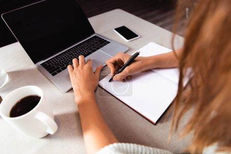 Photo pour Vue recadrée de fille étudiant en ligne avec bloc-notes, smartphone et ordinateur portable dans le café - image libre de droit