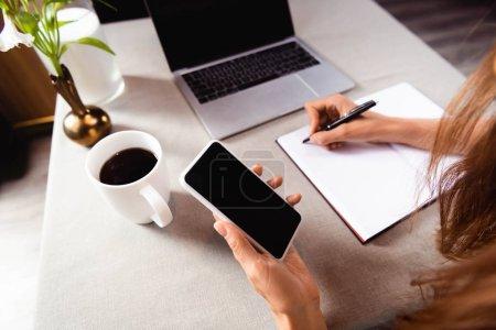 Photo pour Vue croisée d'une femme travaillant avec un bloc-notes, un téléphone intelligent et un ordinateur portable dans un café - image libre de droit