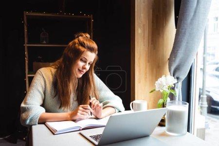 Photo pour Attrayant rousse femme étudiant en ligne avec ordinateur portable dans le café - image libre de droit