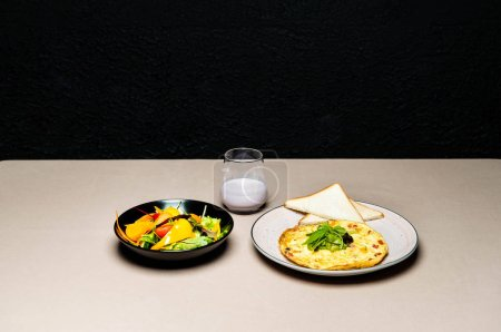 Photo for Tasty salad, omelet, toasts and yogurt in glass on table - Royalty Free Image