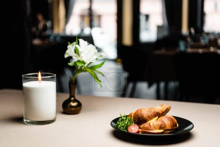 Photo for Plate with croissants for breakfast on table with candle and flowers in restaurant - Royalty Free Image